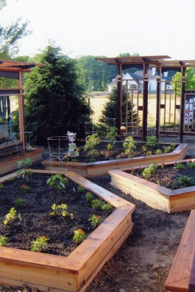 raised-garden-beds-on-a-slope-landscape-craftsman-with-dirt-path-solar-path-lights
