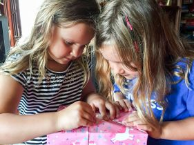 The girls opening their bday present form me, saving the paper